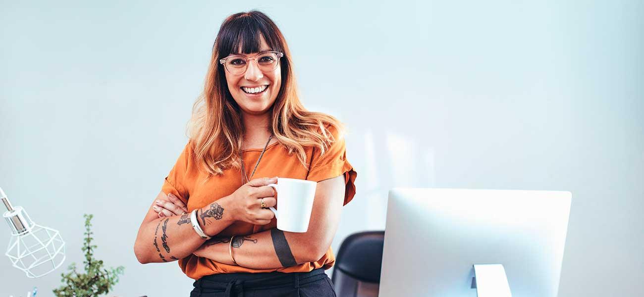 yrityksen-perustaminen-nainen-hymyilee-kahvikuppi-kadessa