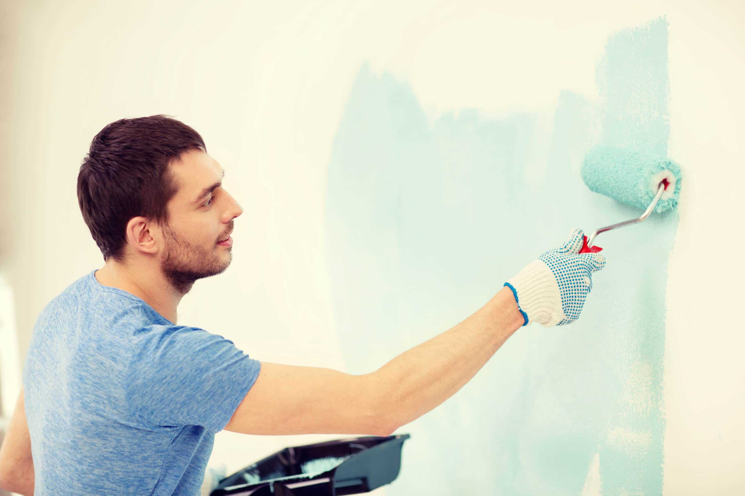 Laskuttaminen yksityishenkilönä. Mies maalaa seinää.