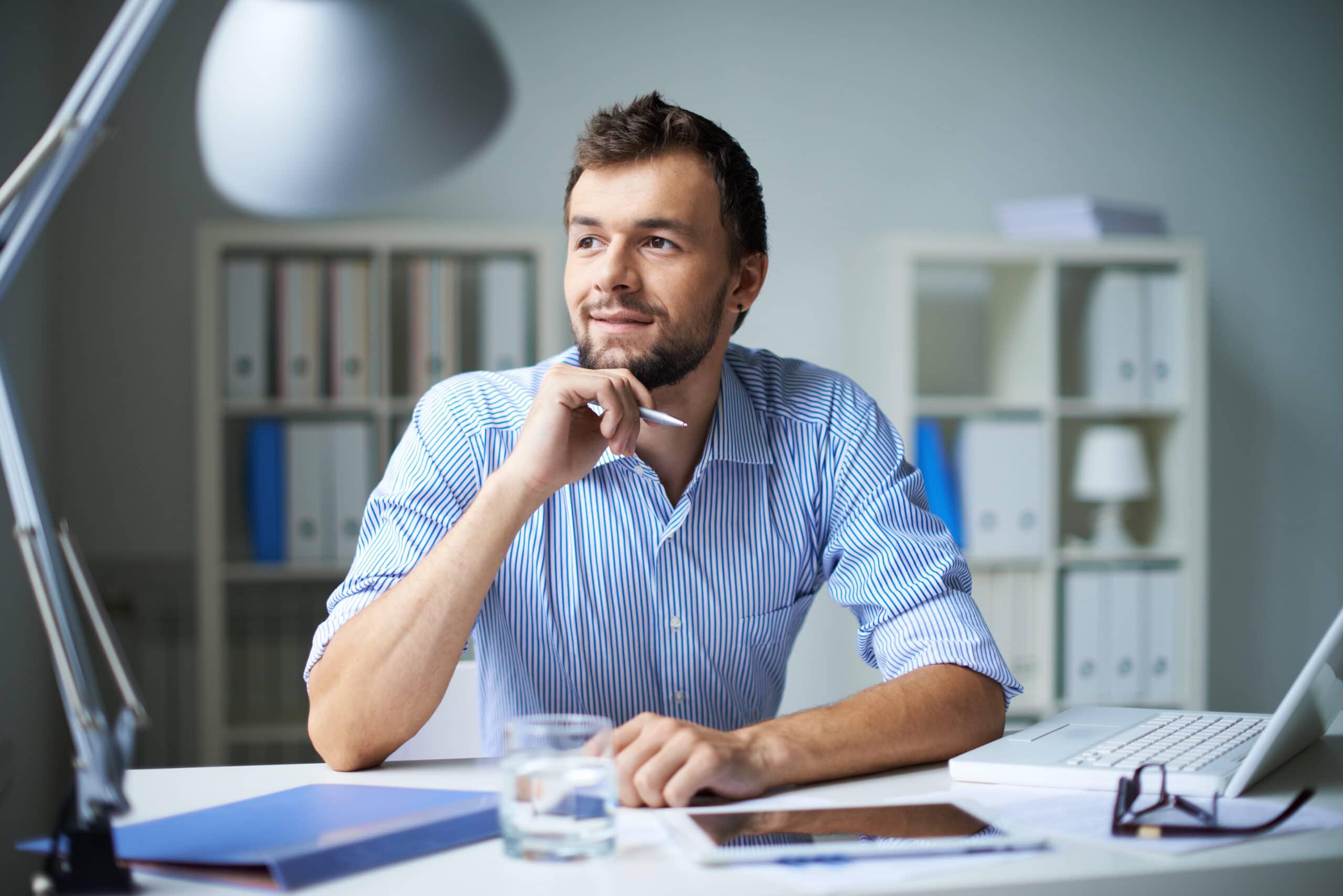 Laskuttaminen yksityishenkilönä. Mies pohtii työpöydän ääressä.