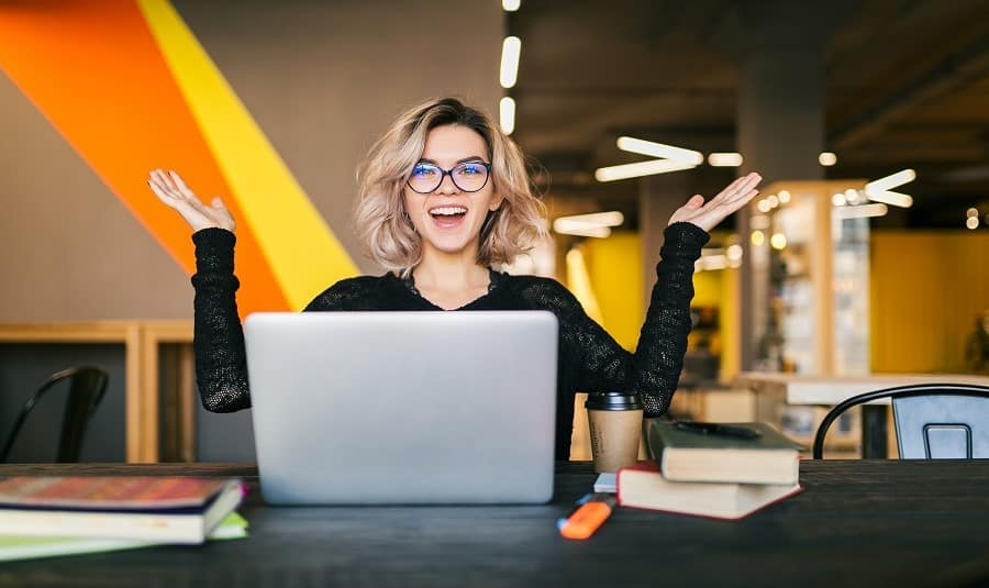 CV-eli-ansioluettelo-priimakuntoon-iloinen-nuori-nainen-tyoskentelee-tietokoneella