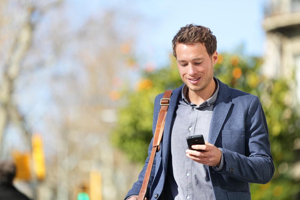 Kuvassa mies selailee puhelimestaan työpaikkoja