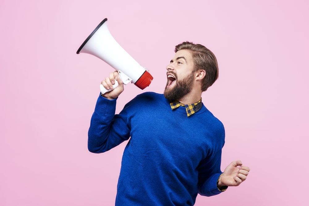 iloinen-kevytyrittaja-mies-huutaa-megafoniin