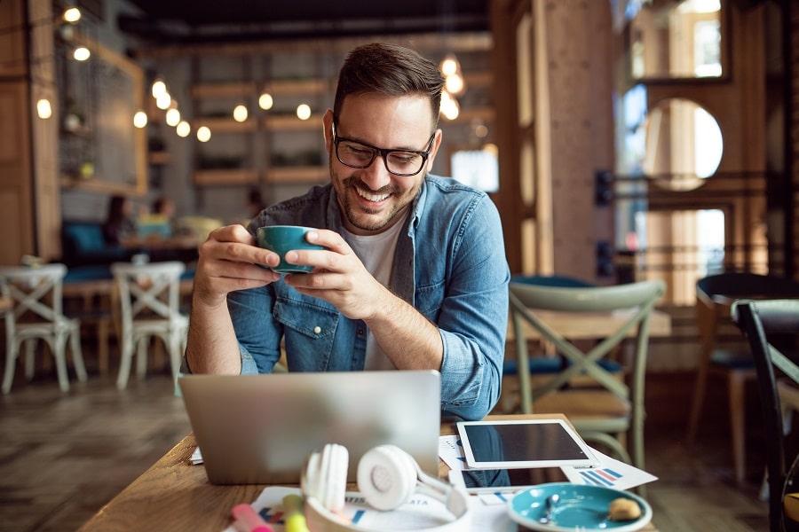 Mies juo kahvia ja työskentelee kannettavalla tietokoneella