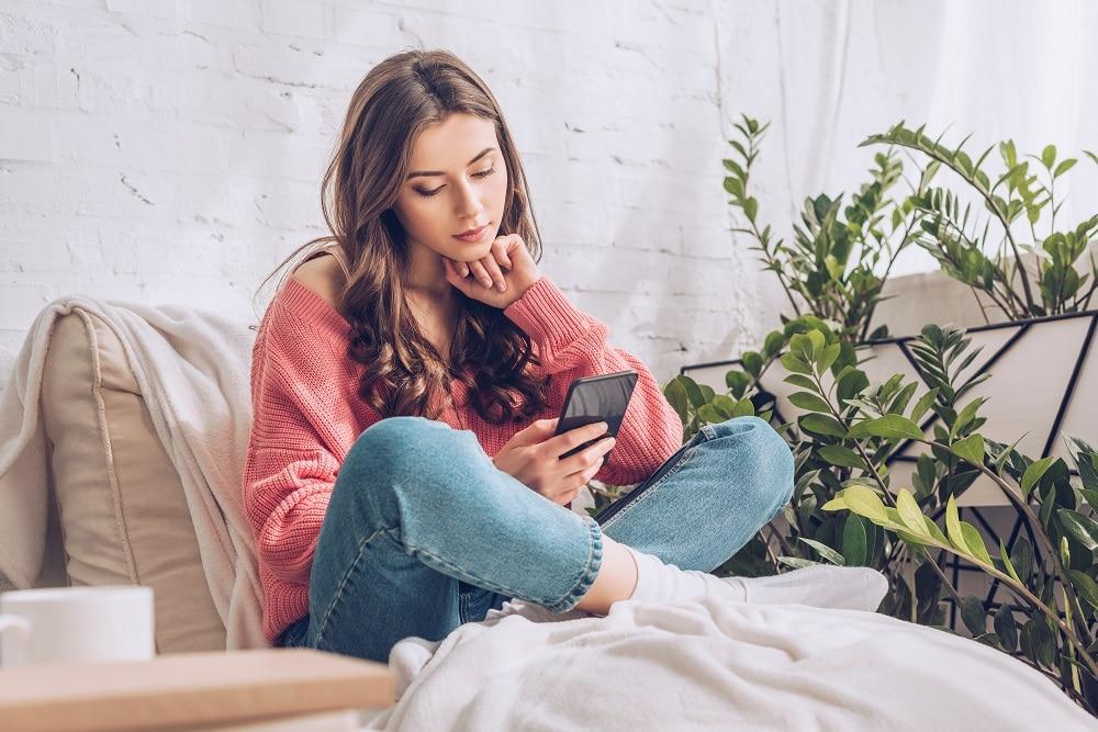 Kuvassa nainen tekee töitä puhelimellaan sivutoimisesti