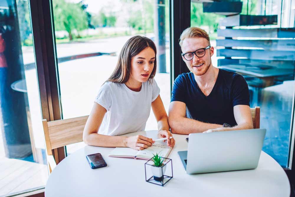 liiketoimintasuunnitelma työn alla - nainen ja mies tietokoneella