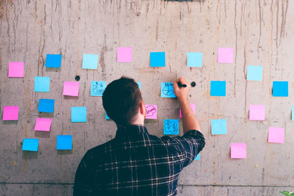 Aloittava yrittäjä hahmottelee liiketoimintasuunnitelmaa post it-lapuille