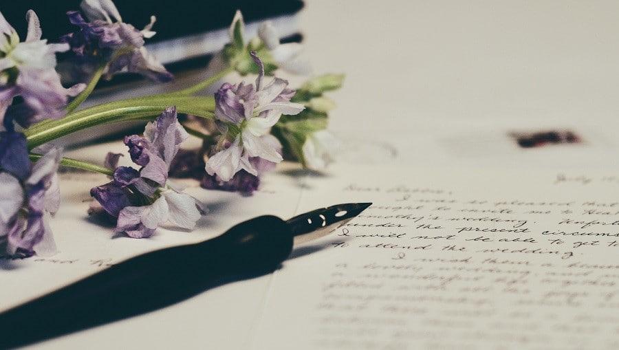 Mustekynä ja kukkia kirjoituksen päällä
