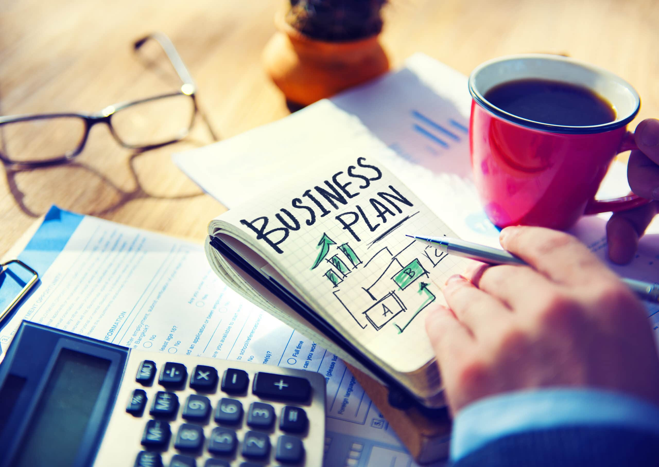 Yrittäjä laatii liiketoimintasuunnitelmaa starttirahahakemusta varten.