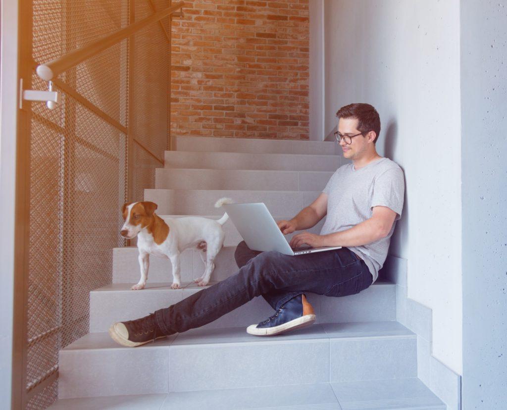 Freelancer mies työskentelee koiran kanssa portaissa