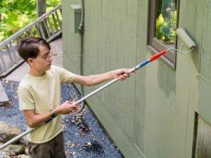 KUvassa kevytyrittäjä maalaa talon seinää