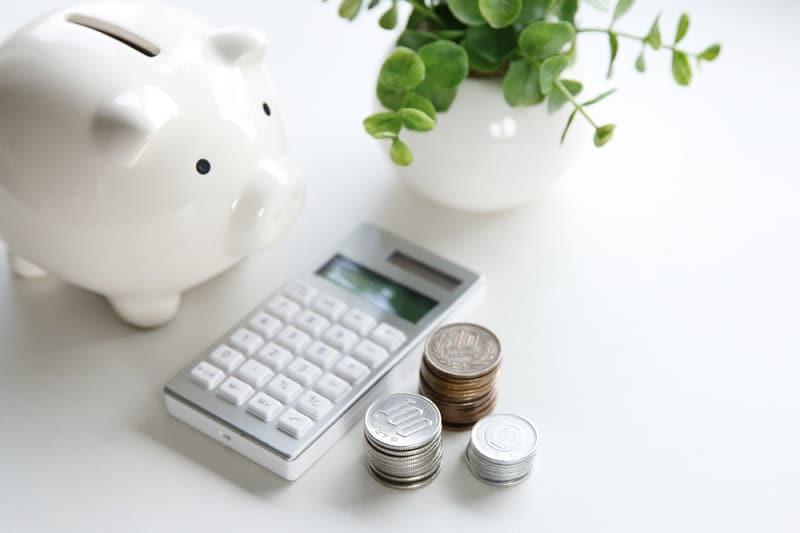 Säästöpossu, laskin ja kolikoita