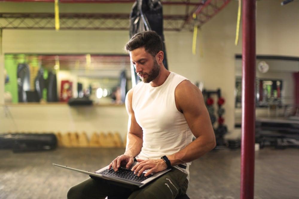 Hihattomassa paidassa oleva mies päivittää sosiaalista mediaa