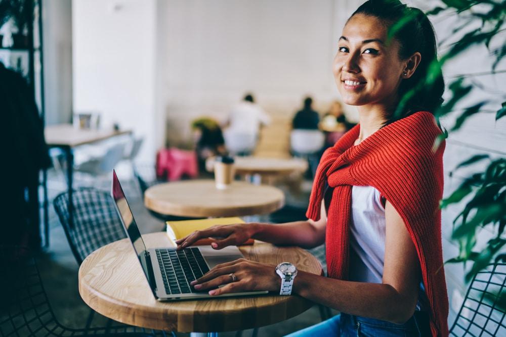 Nainen kirjoittaa kahvilassa tarinoita sosiaaliseen mediaan