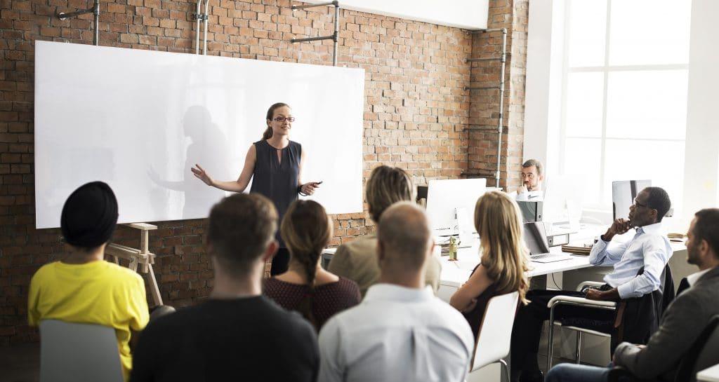 Opettaja seisoo taulun edessä ja puhuu