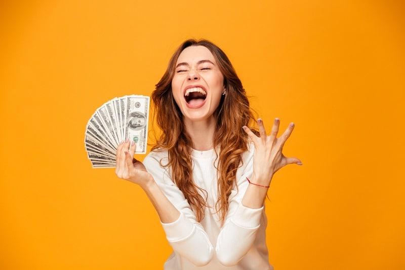 Oranssi tausta ja naisella rahaa kädessä