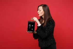 Kuvassa nainen laittaa rahaa säästöpossuun