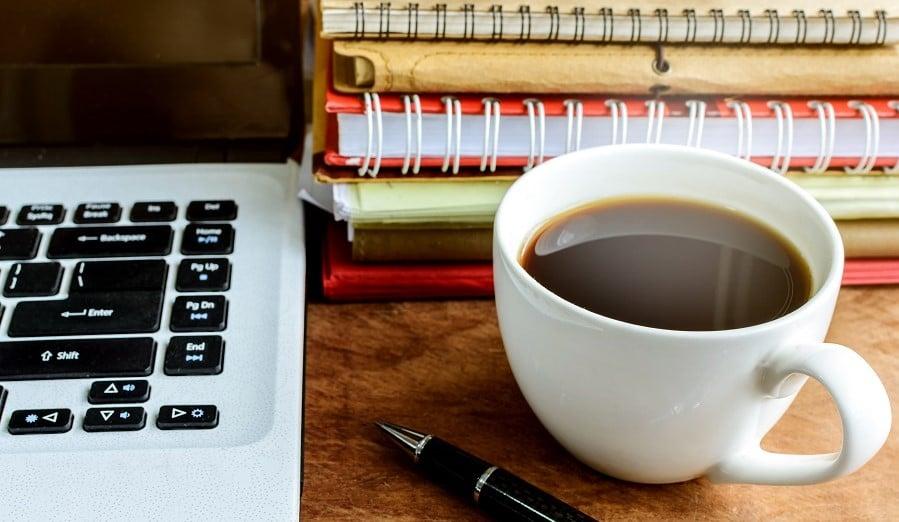 Kannettava tietokone, kahvikuppi ja muistiinpanoja