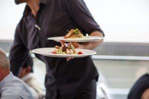 Tarjoilijalla ruokalautset kädessä