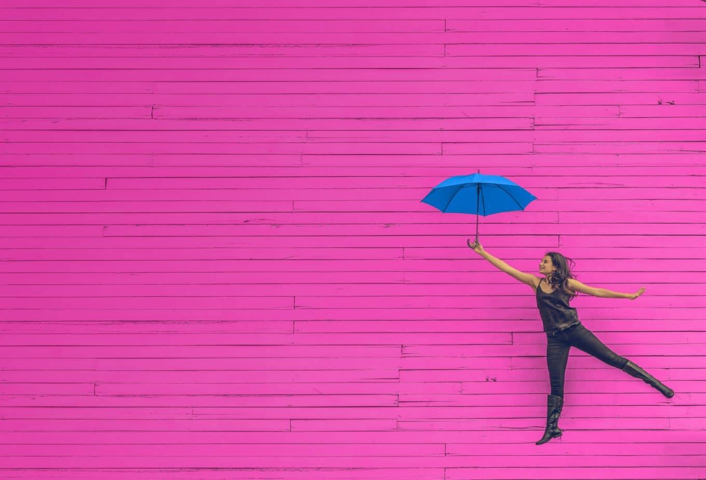 kevytyrittaja-nainen-ja-sininen-sateenvarjo-pinkilla-taustalla