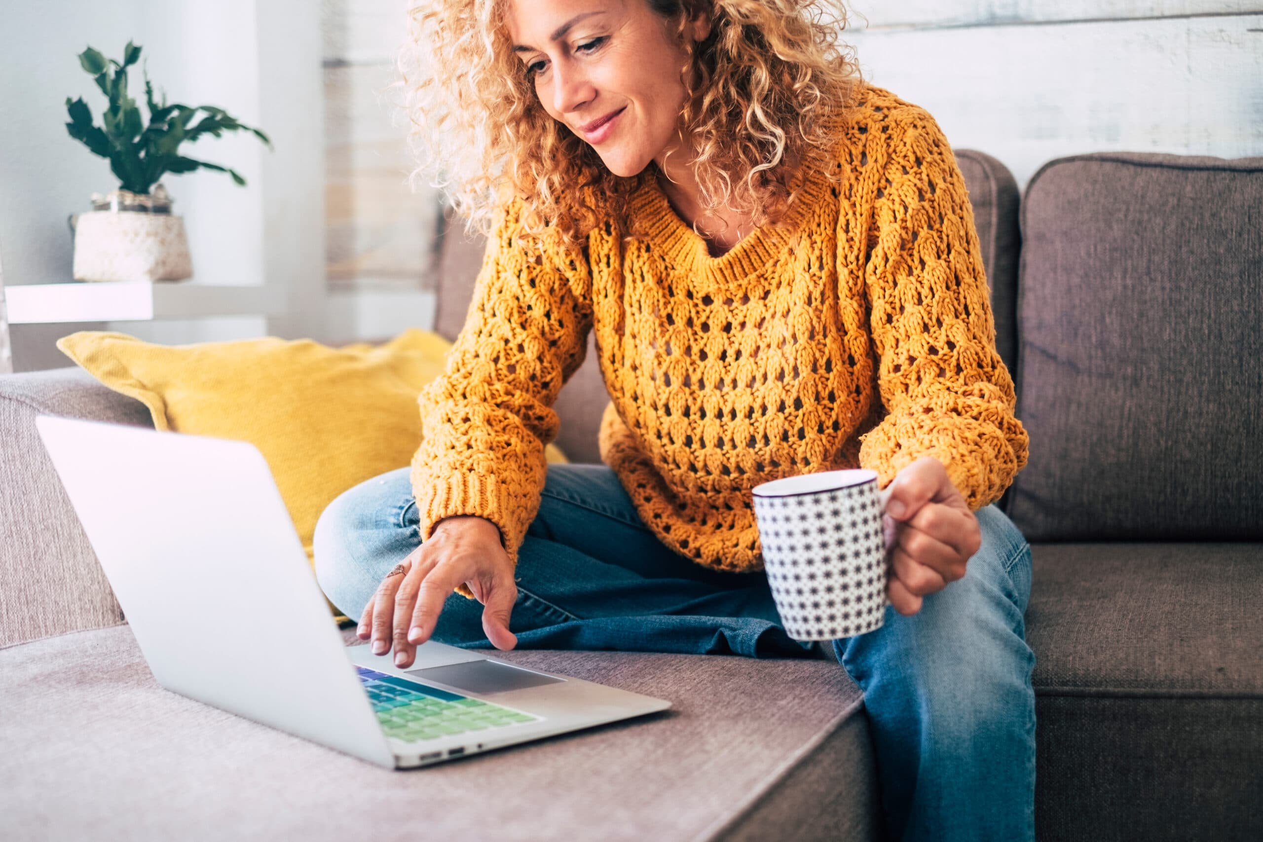 Somen parhaat yrittäjäyhteisöt. Nainen katsoo tietokonetta hymyillen.