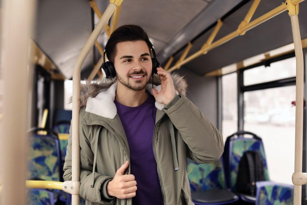 Ammatillinen kehittyminen. Mies kuuntelee poadcastia bussissa.