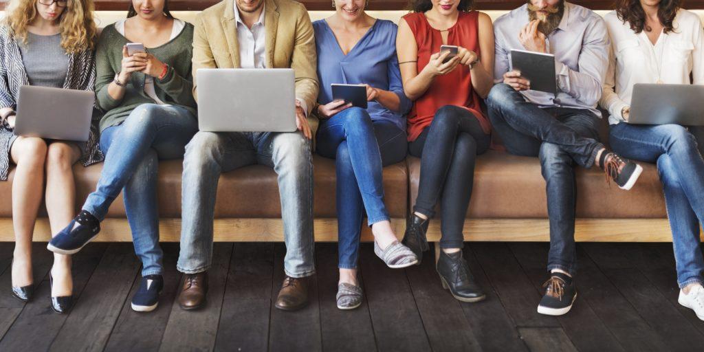 Ihmiset istuvat rivissä selaten puhelinta tai kannettavaa tietokonetta