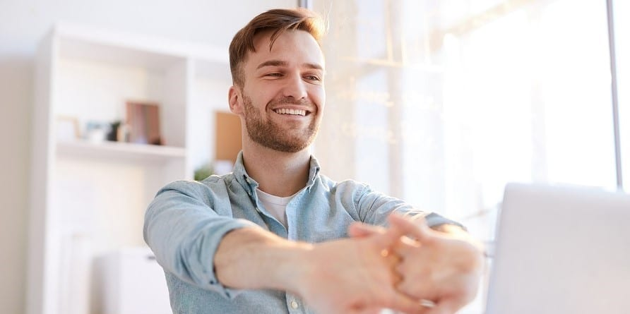 iloinen-yrittaja-mies-venyttelee-tietokoneen-aaressa