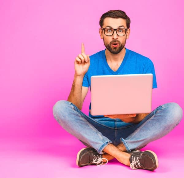 mies tietokoneella - pinkki tausta