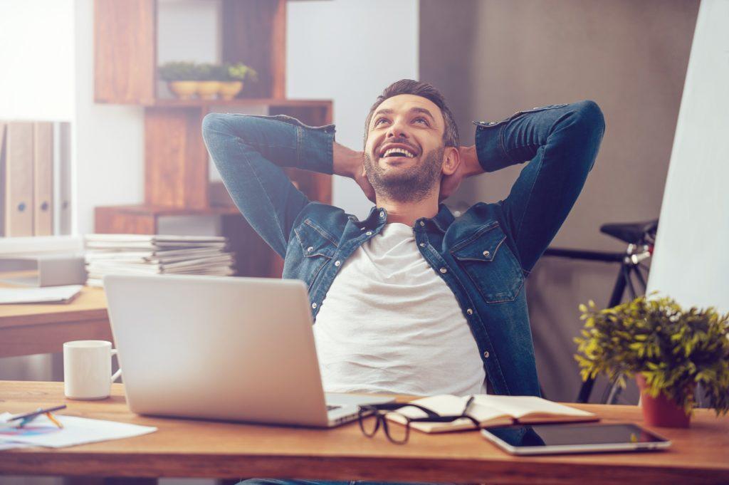 onnellinen mies toimistossa