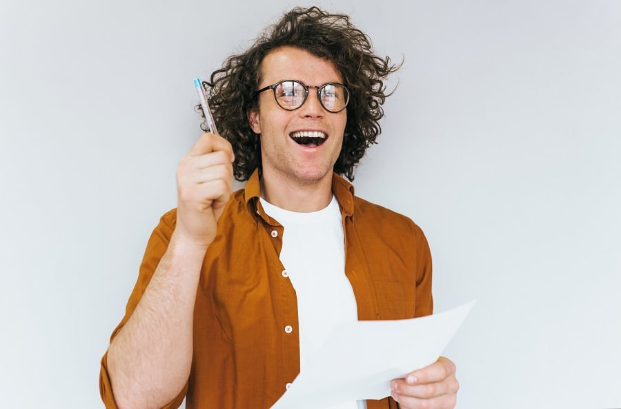 iloinen-mies-paperi-ja-kynä-kädessä