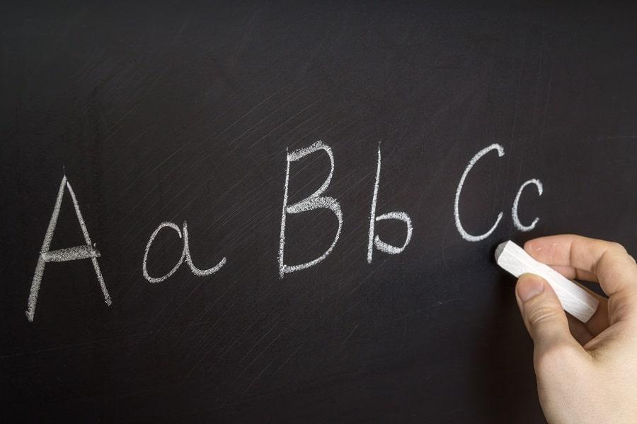 Käsi kirjoittaa liitutaululle isoja ja pieniä aakkosia