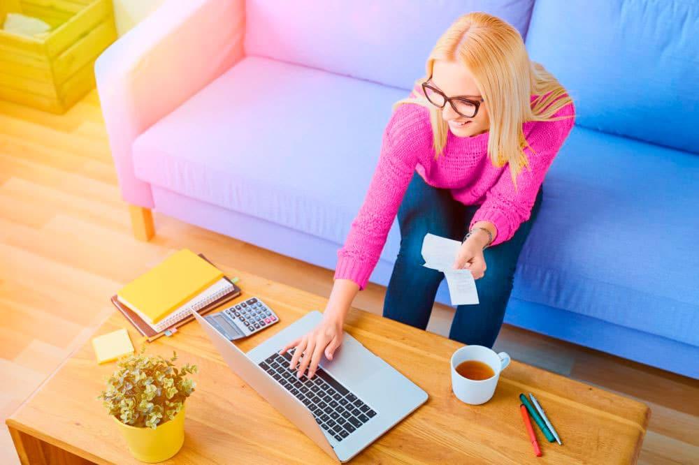 yel-vakuutus-maksut-iloinen-nainen-sohvalla