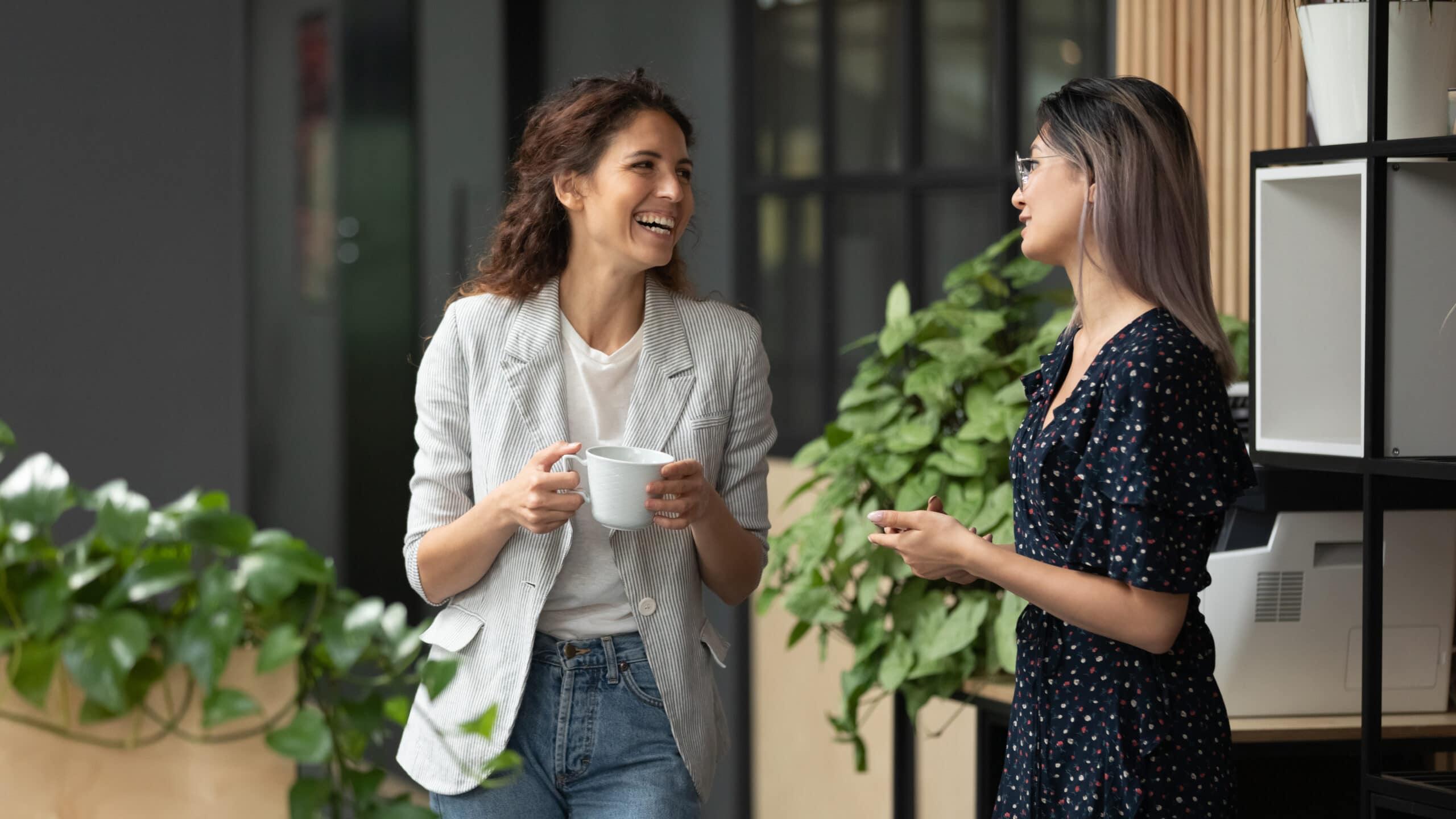 Työhaastattelukysymykset. Kaksi naista juttelee työpaikalla.