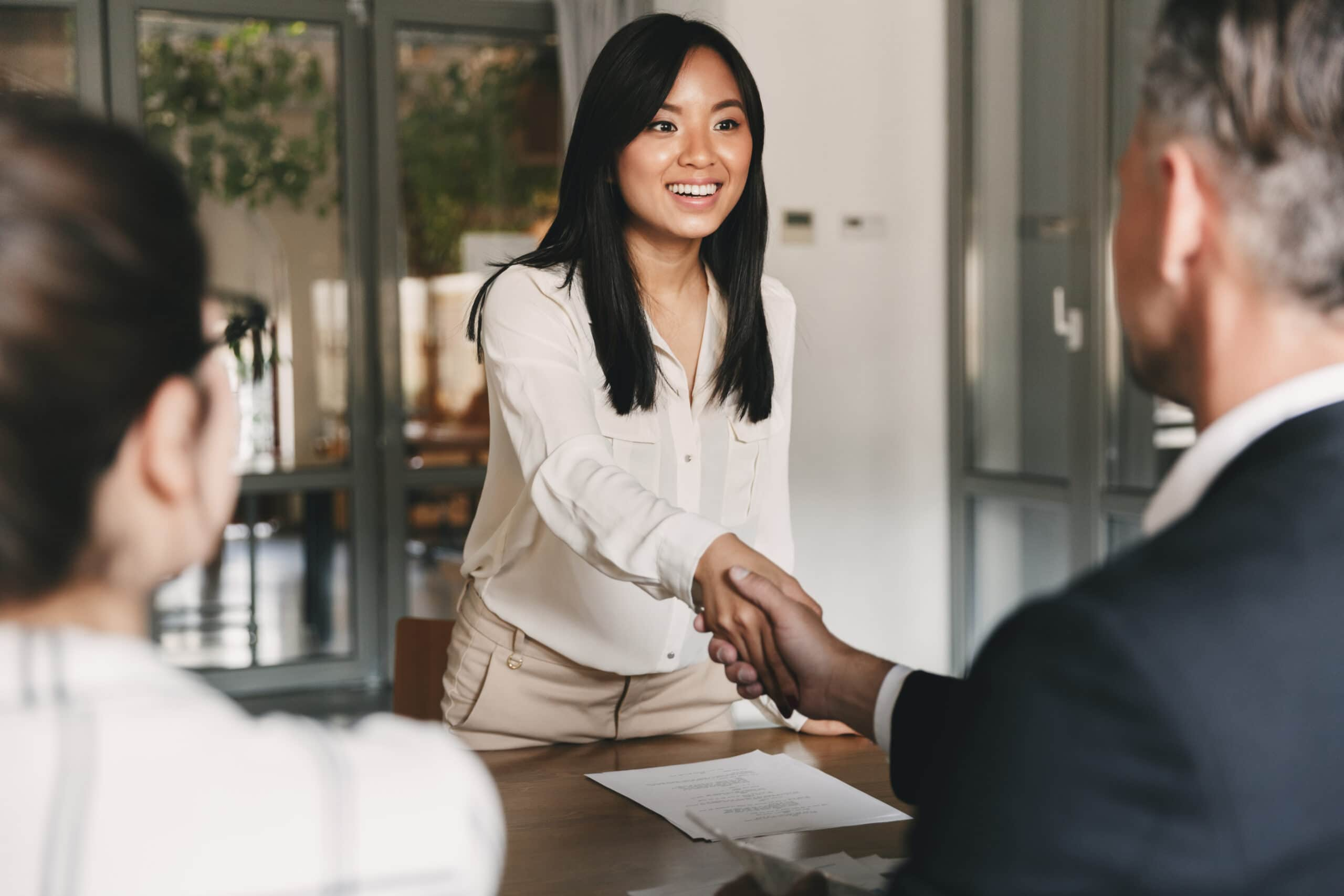 Työhaastattelun tavallisimmat kysymykset. Nainen kättelee miestä.