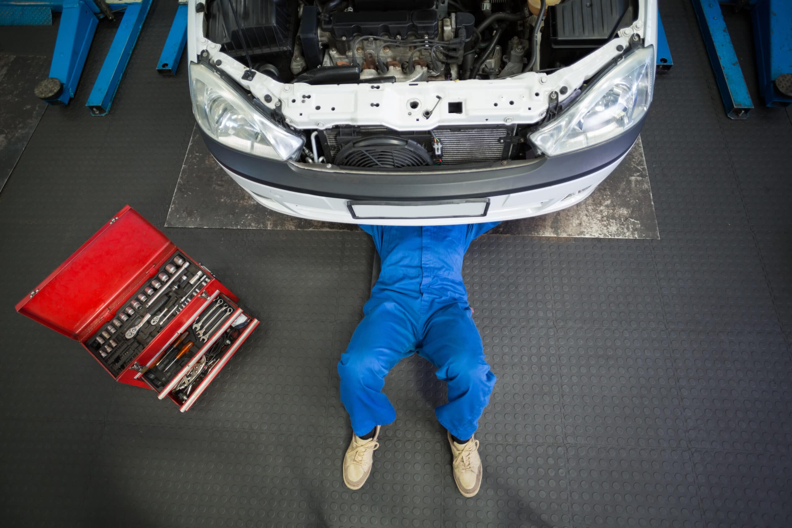 Auton huolto- ja korjaustyöt. Mekaanikko auton alla