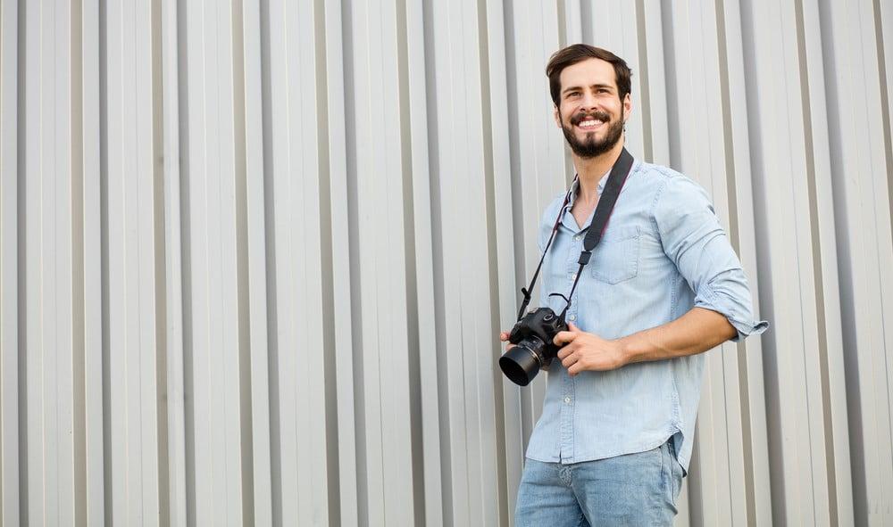 Iloinen nuori valokuvaajamies