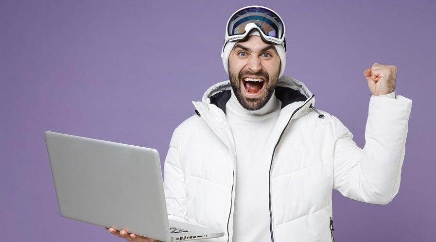 yrittajamies-hiihtovaatteet-paalla-ja-kannettava-tietokone-kadessa