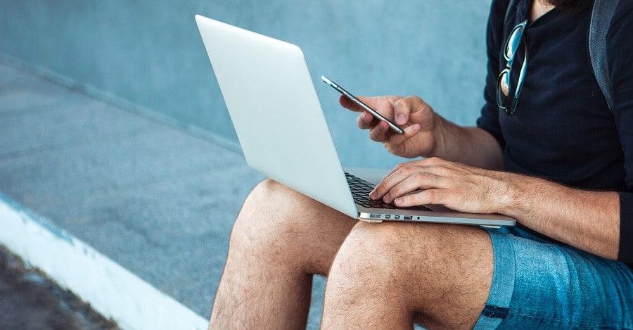 Kirjanpidon säilytysaika. Miesyrittäjä selaa kannettavaa tietokonetta ja älypuhelinta