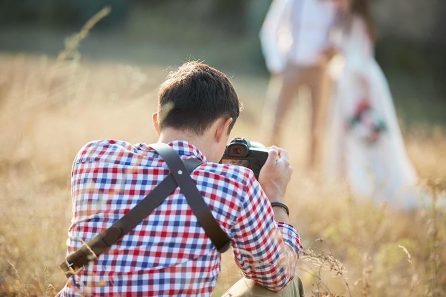 Kevytyrittäjä ja valokuvaaja. Mies valokuvaa hääparia