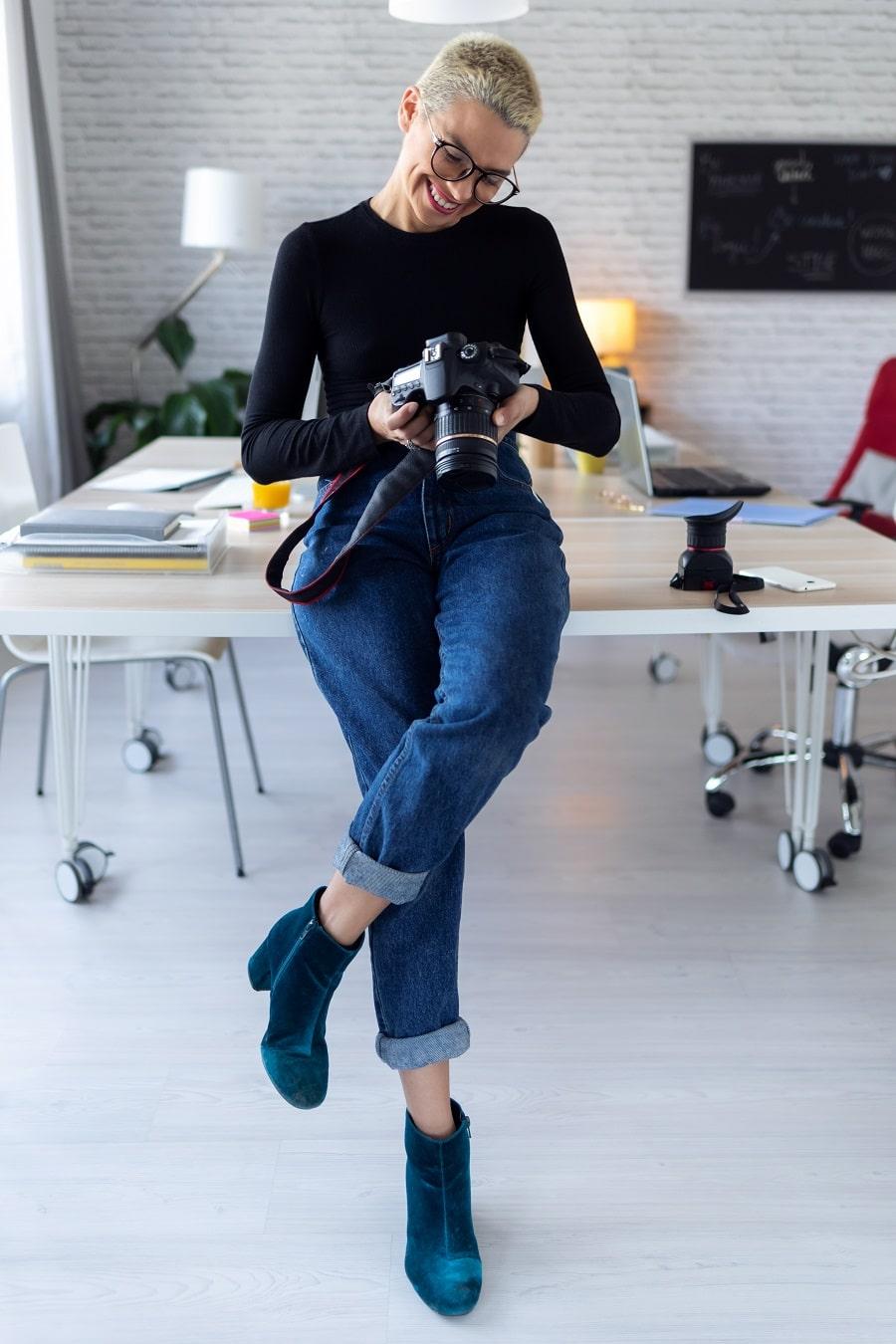 Kevytyrittäjä ja valokuvaaja. Nainen selaa järjestelmäkameraansa