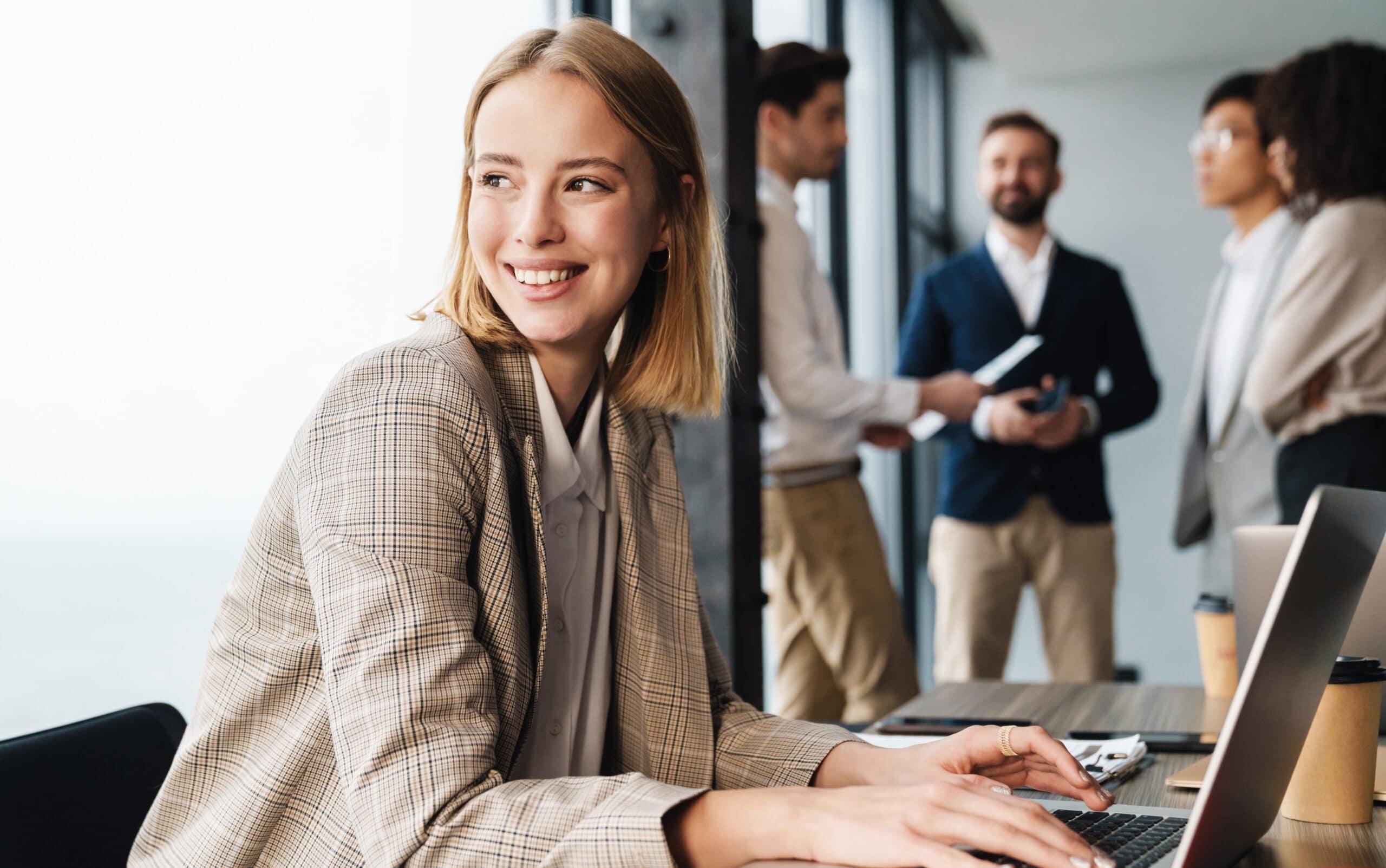 Iloinen nainen työskentelee kollegat taustalla