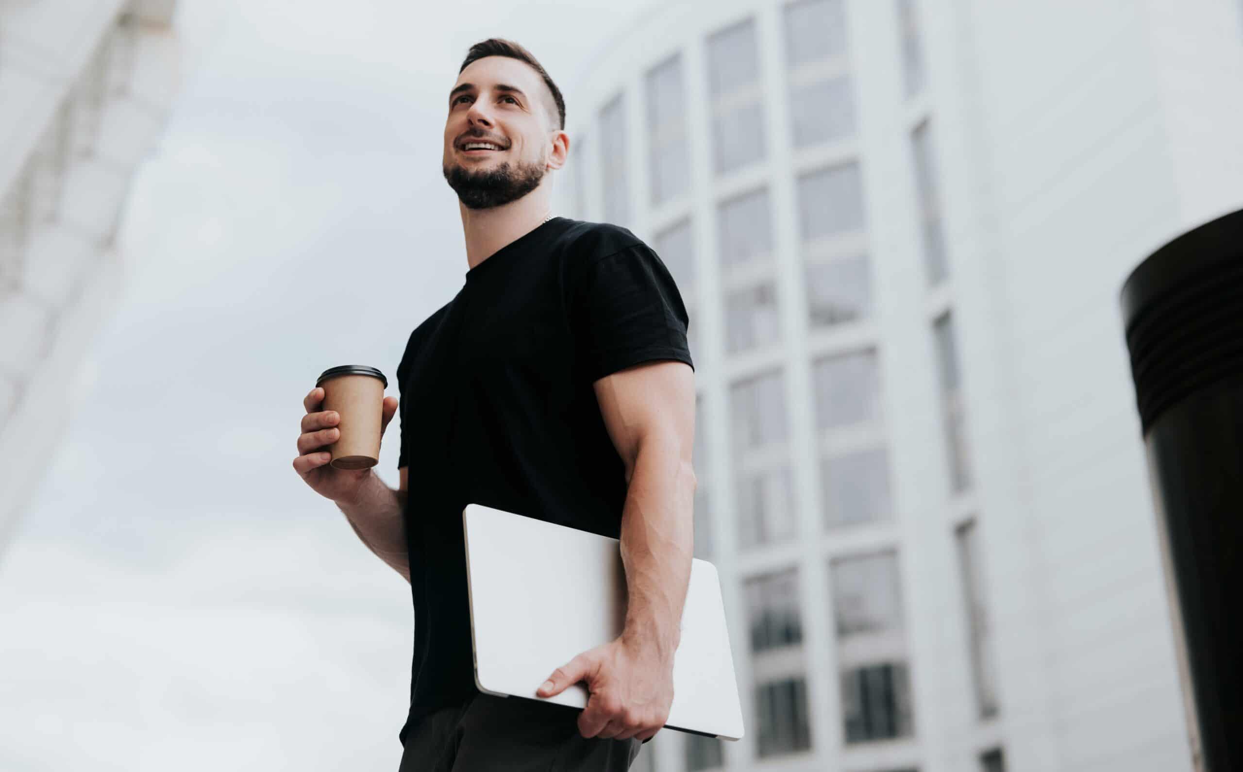 Nuori yrittäjämies ulkona kahvimuki ja tietokone kädessä