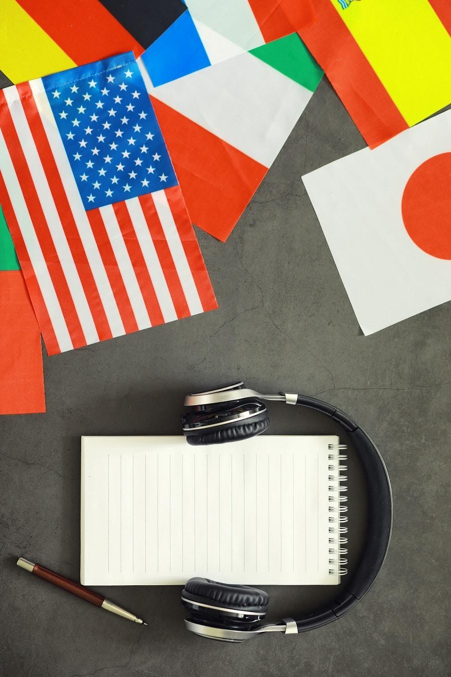 Työskentele kääntäjänä kevytyrittäjänä. Kuulokkeet, muistivihko ja eri maiden lippuja
