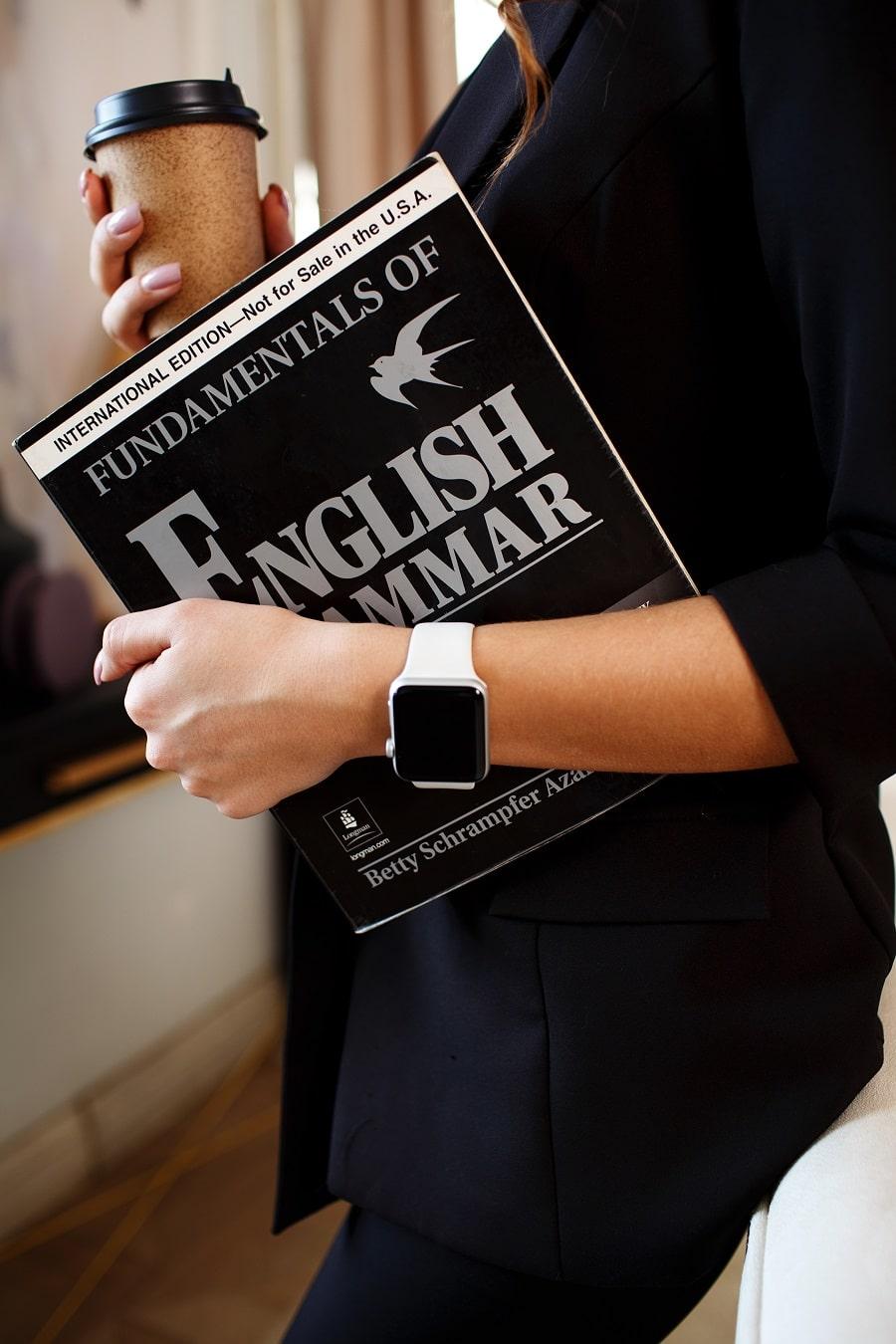 Työskentele kääntäjänä kevytyrittäjänä. Nainen pitelee englannin sanakirjaa ja kahvimukia