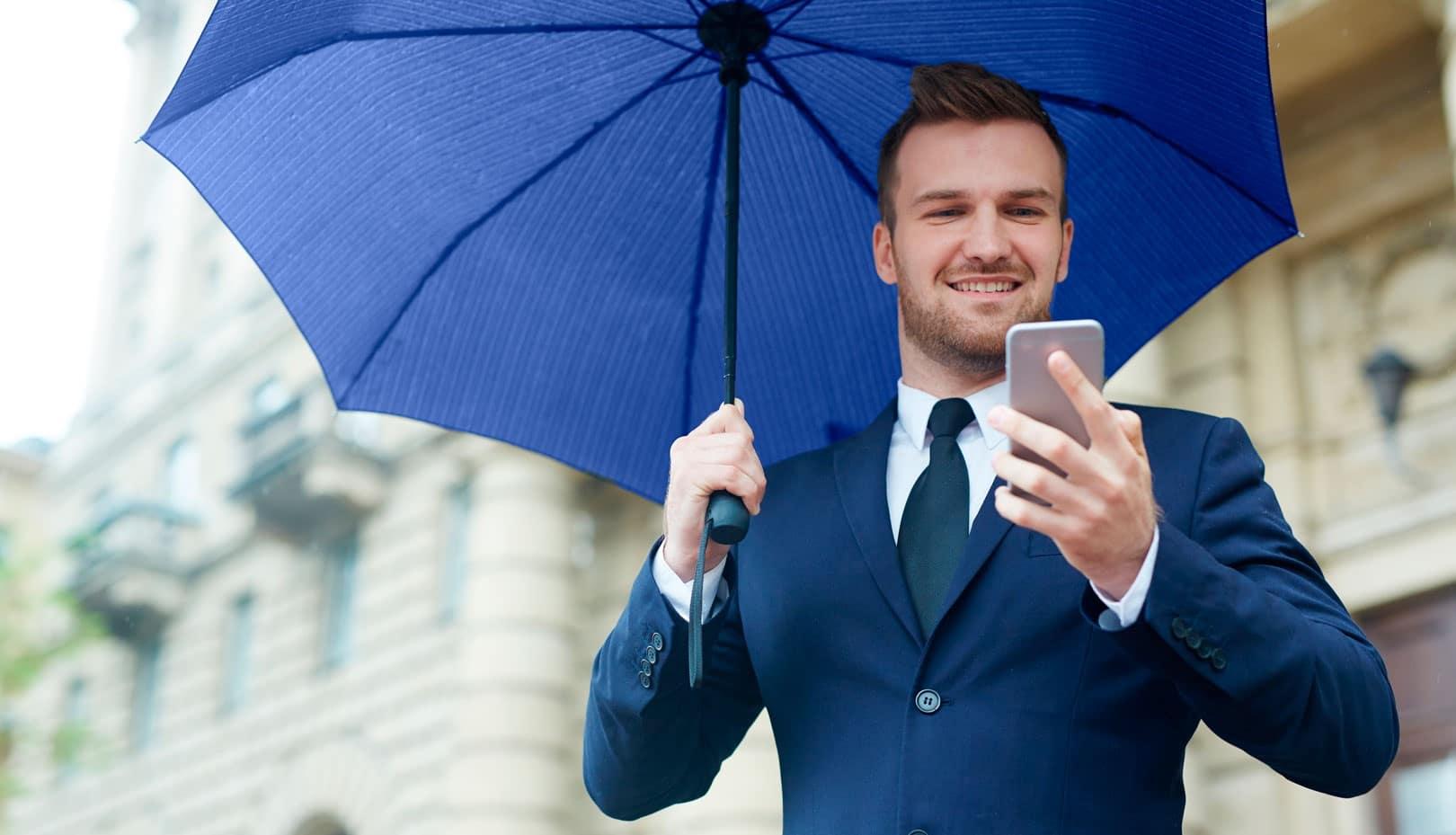 YEL ja kevytyrittäjyys. Mies selaa puhelinta sateenvarjon alla