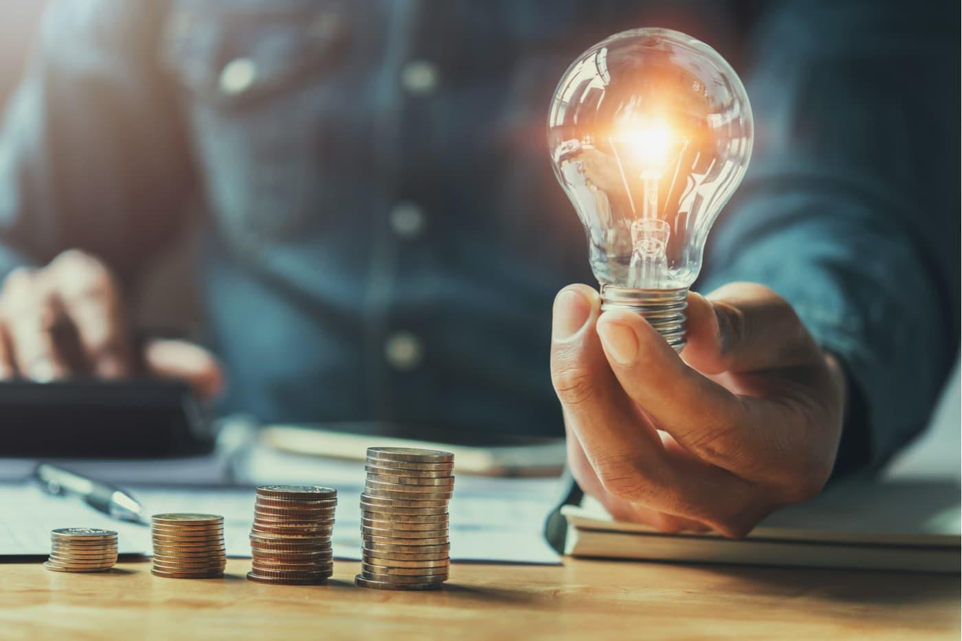 Yrittäjän euro. paljon yrittäjän tulee tienata? Euron kolikoita ja hehkulamppu.