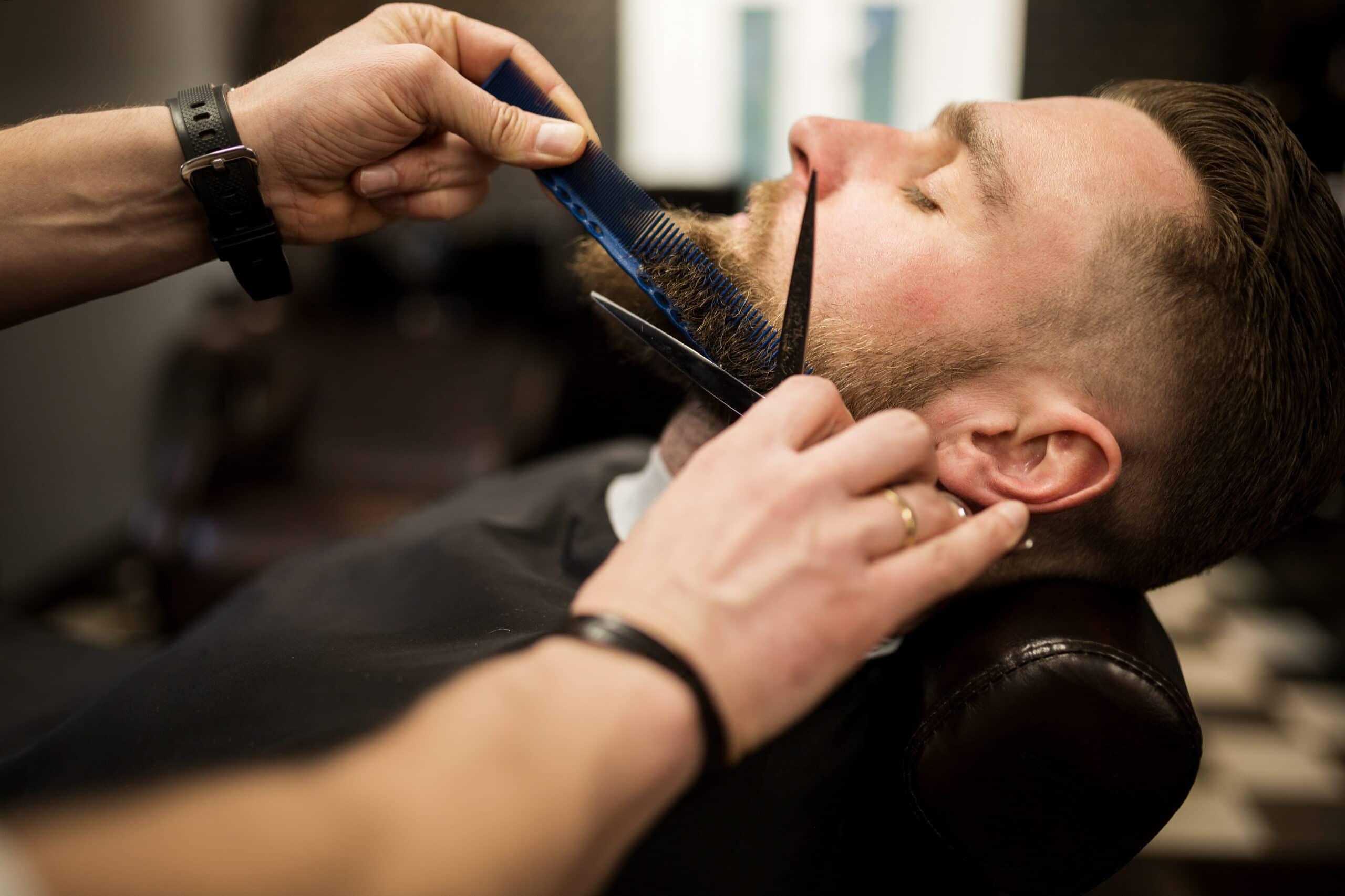 Yrittäjän ensimmäiset asiakkaat. Parturi trimmaa asiakkaan partaa.