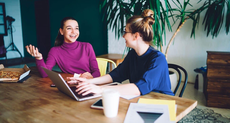yritys-ystavan-kanssa-kaksi-iloista-yrittajanaista-tyoskentelee
