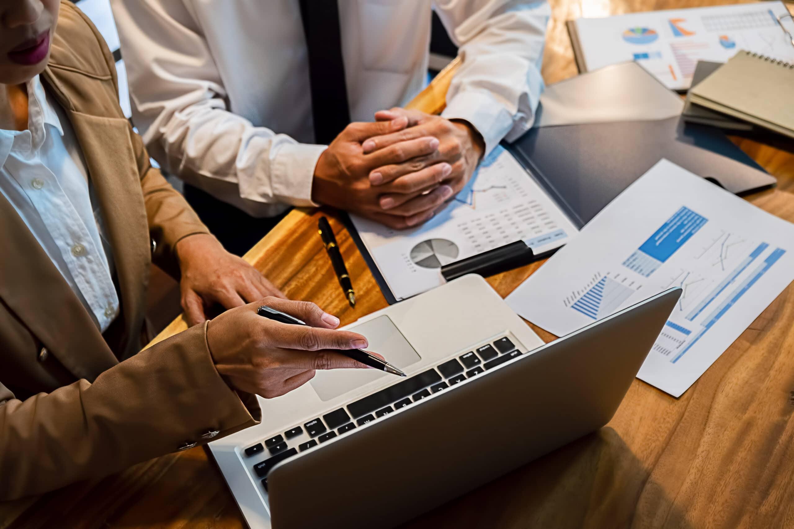 Kirjanpito-ohjelma. Yrittäjä ja kirjanpitäjä pöydän ääressä.