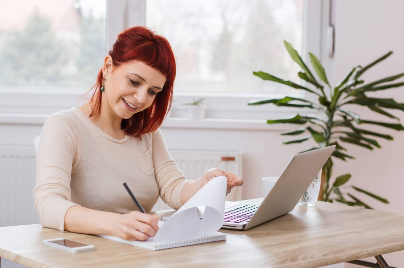 Red,Haired,Girl,Writing,Something,On,A,Piece,Of,Paper